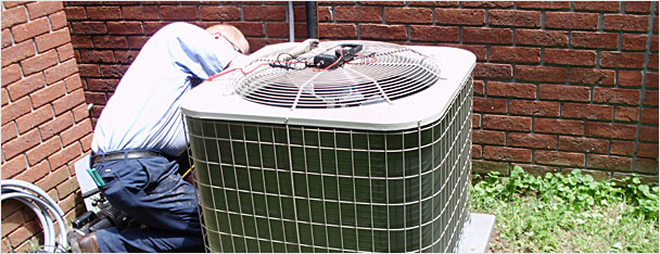 A & L Heating & Cooling employee fixing air conditioning unit